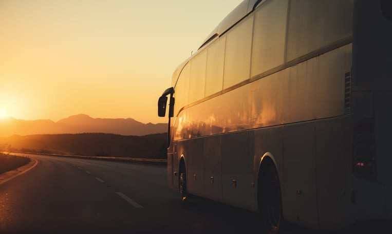 Charter Bus to Airport - Leprechaun Lines - White bus driving on road towards the setting sun
